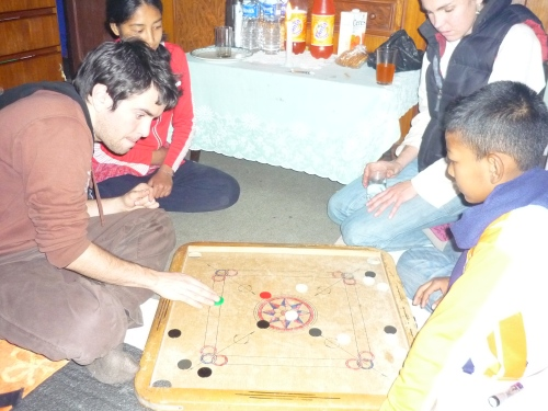 Craig and Anish, playing carum, while Nisha and Rosie watch